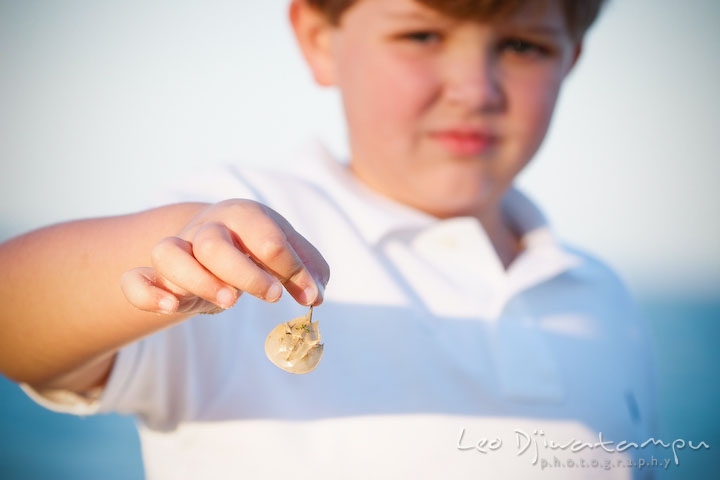 A kid, boy, showing a tiny horse shoe crab. Kent Island, Annapolis, MD Fun Candid Family Lifestyle Photographer, Leo Dj Photography