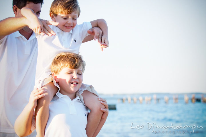 A boy carrying his brother on his shoulder with a help from their father. Kent Island, Annapolis, MD Fun Candid Family Lifestyle Photographer, Leo Dj Photography