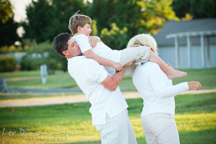 Dad helping son to get down from mom's shoulder. Kent Island, Annapolis, MD Fun Candid Family Lifestyle Photographer, Leo Dj Photography