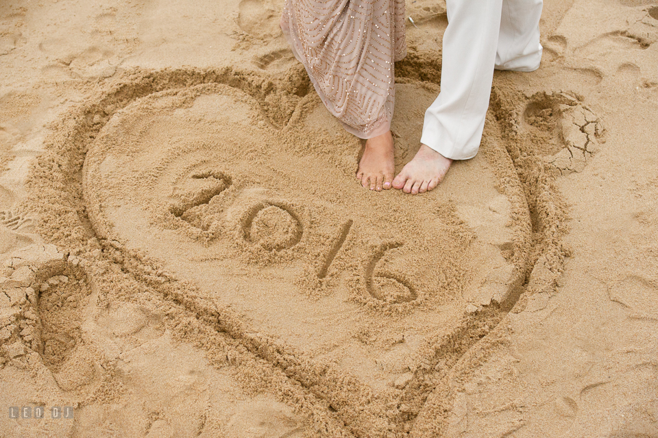 Silver Swan Bayside Groom and Bride's feet on a heart shaped sand drawing photo by Leo Dj Photography