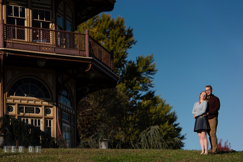 Patterson Park Baltimore Maryland engaged couple snuggling by the pagoda photo by Leo Dj Photography.