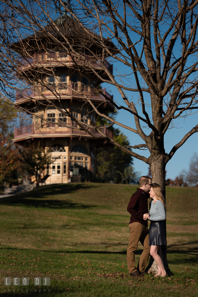 Patterson Park Baltimore Maryland engaged man kissing fiancée by tree photo by Leo Dj Photography.