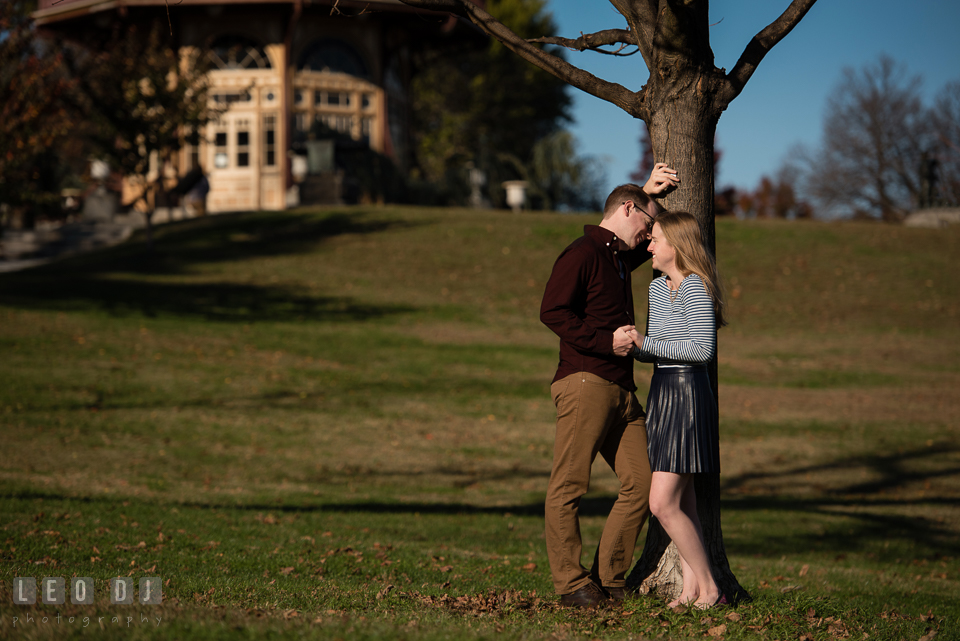 Patterson Park Baltimore Maryland engaged man laughing with fiancee by tree photo by Leo Dj Photography.