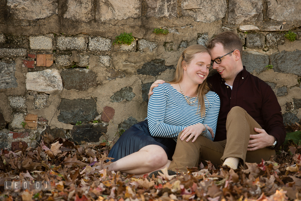 Patterson Park Baltimore Maryland engaged couple cuddling by autumn leaves photo by Leo Dj Photography.