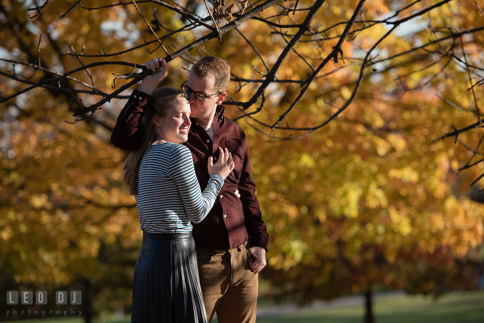 Patterson Park Baltimore Maryland engaged girl by autumn leaves kissed by fiance photo by Leo Dj Photography.