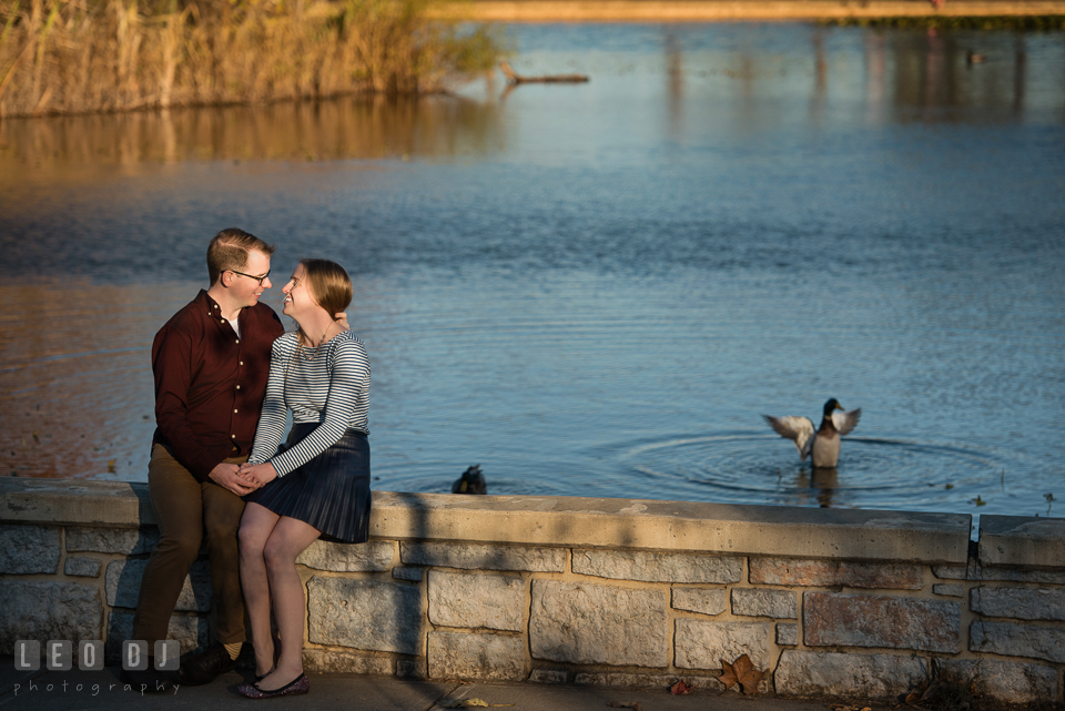 Patterson Park Baltimore Maryland engaged couple sitting by a pond laughing photo by Leo Dj Photography.