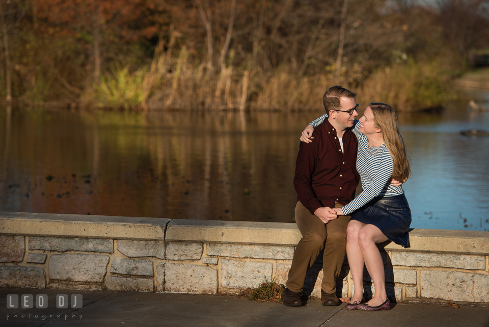 Patterson Park Baltimore Maryland engaged man cuddling with fiancee by pond photo by Leo Dj Photography.