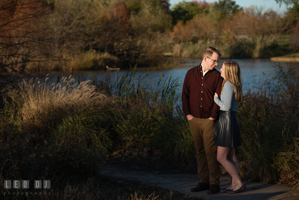 Patterson Park Baltimore Maryland engaged snuggled with fiance by a pond photo by Leo Dj Photography.