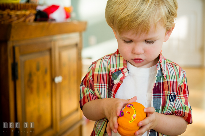 Little boy playing with a little pumpkin decoration. Queenstown, Eastern Shore Maryland candid children and family lifestyle portrait photo session by photographers of Leo Dj Photography. http://leodjphoto.com