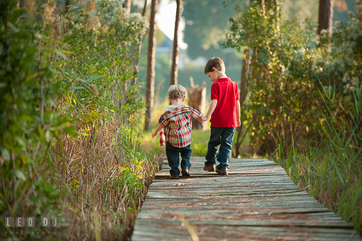 Two toddler boys walking together holding hands. Queenstown, Eastern Shore Maryland candid children and family lifestyle portrait photo session by photographers of Leo Dj Photography. http://leodjphoto.com