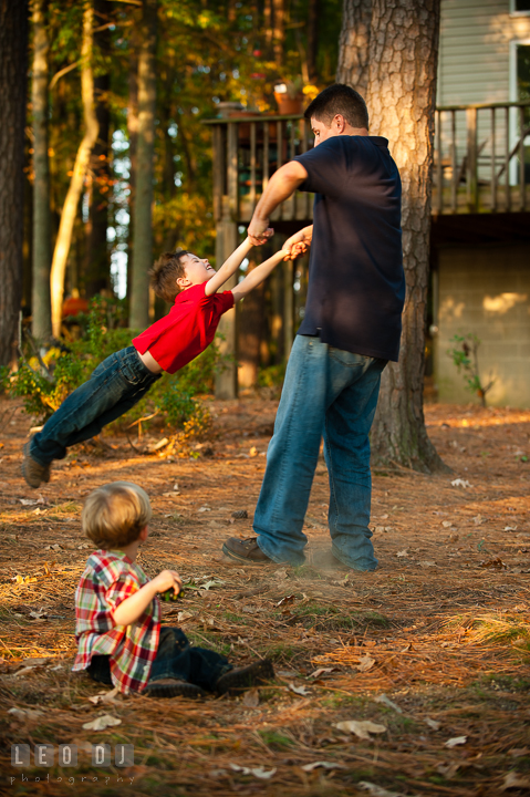 Dad swinging his son. Queenstown, Eastern Shore Maryland candid children and family lifestyle portrait photo session by photographers of Leo Dj Photography. http://leodjphoto.com
