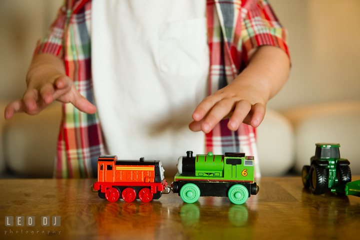 Little boy playing with trains and locomotive from Thomas. Queenstown, Eastern Shore Maryland candid children and family lifestyle portrait photo session by photographers of Leo Dj Photography. http://leodjphoto.com