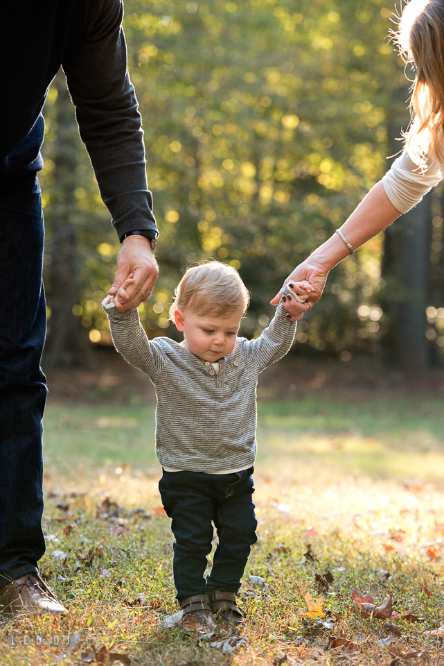 Quiet Waters Park Annapolis Maryland little boy trying to walk held by mom and dad photo by Leo Dj Photography.