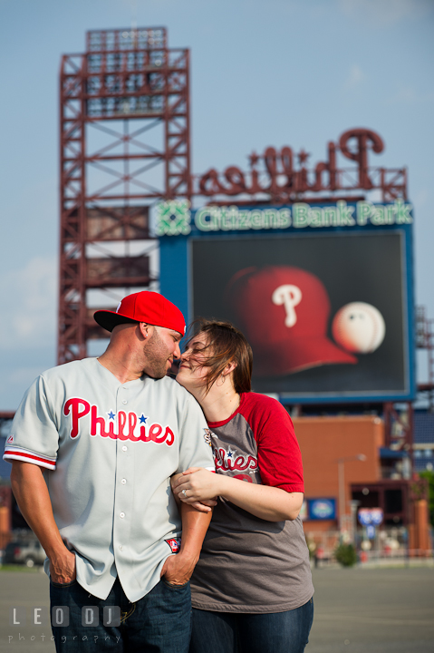 Engaged guy and his fiancée wearing Phillies clothing cuddling. Pre-wedding or engagement photo session at Phillies Ball Park, Love Park, Philadelphia, by wedding photographers of Leo Dj Photography.