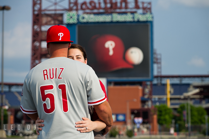 Engaged guy wearing Phillies Ruiz 51 jersey hugged his fiancée. Pre-wedding or engagement photo session at Phillies Ball Park, Love Park, Philadelphia, by wedding photographers of Leo Dj Photography.