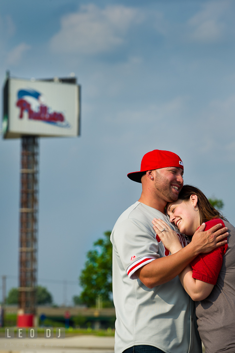 Engaged girl cuddled with her fiancé. Pre-wedding or engagement photo session at Phillies Ball Park, Love Park, Philadelphia, by wedding photographers of Leo Dj Photography.