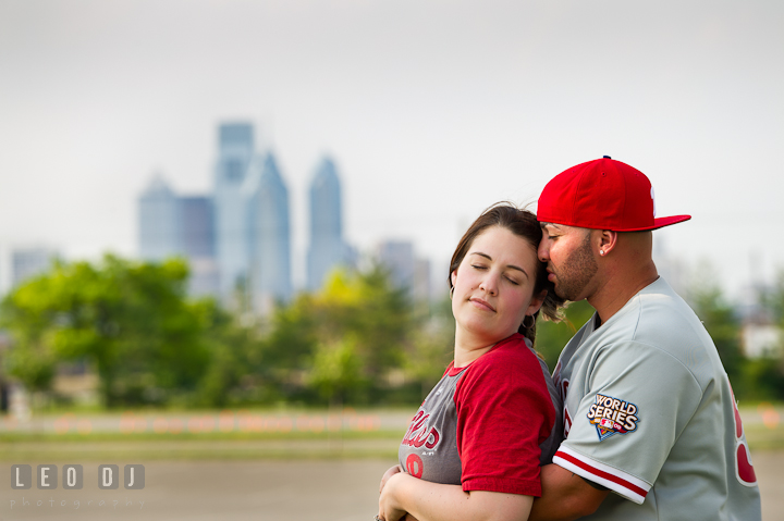 Engaged couple with Phillies merchandise cuddling, with Philadelphia skyscrapers in the background. Pre-wedding or engagement photo session at Phillies Ball Park, Love Park, Philadelphia, by wedding photographers of Leo Dj Photography.
