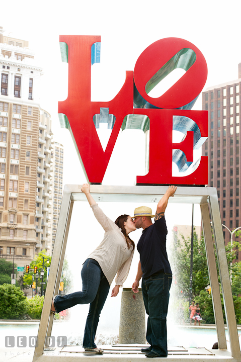 Engaged guy kissing his fiancée. Pre-wedding or engagement photo session at Phillies Ball Park, Love Park, Philadelphia, by wedding photographers of Leo Dj Photography.