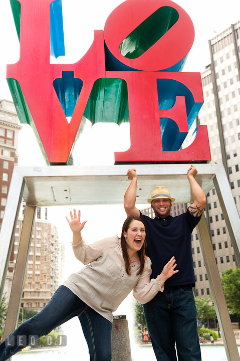Engaged girl and her fiancé doing a goofy pose. Pre-wedding or engagement photo session at Phillies Ball Park, Love Park, Philadelphia, by wedding photographers of Leo Dj Photography.