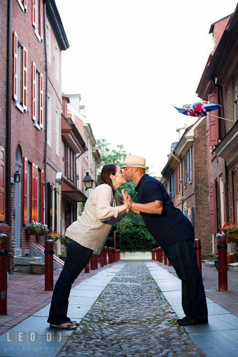 Engaged couple kissing in the Elfreth's Alley. Pre-wedding or engagement photo session at Phillies Ball Park, Love Park, Philadelphia, by wedding photographers of Leo Dj Photography.