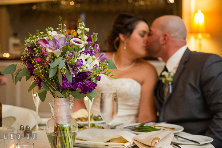 Bride's flower bouquet on sweet heart table. Bride and Groom kissing. The Tidewater Inn Wedding, Easton Maryland, reception photo coverage by wedding photographers of Leo Dj Photography. http://leodjphoto.com