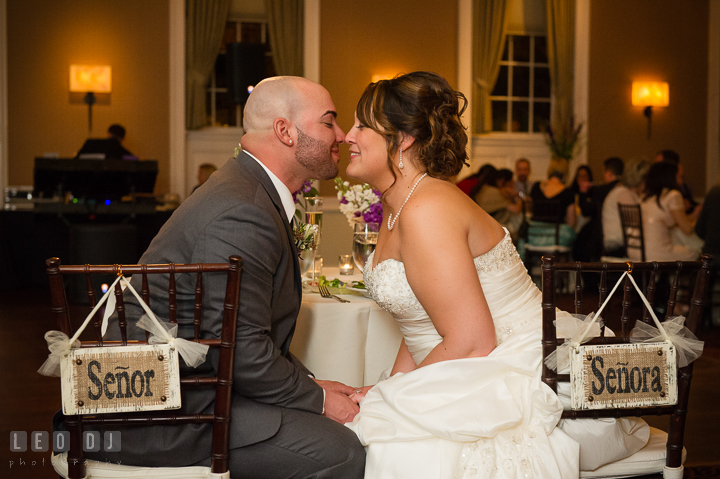 Bride and Groom at sweet heart table holding hands and almost kissed. The Tidewater Inn Wedding, Easton Maryland, reception photo coverage by wedding photographers of Leo Dj Photography. http://leodjphoto.com