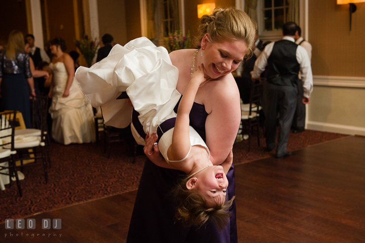 Bridesmaid flipped flower girl upside down and laughing. The Tidewater Inn Wedding, Easton Maryland, reception photo coverage by wedding photographers of Leo Dj Photography. http://leodjphoto.com
