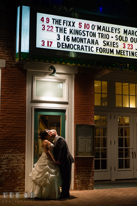 Groom kissing Bride outside in the city in front of a theater. The Tidewater Inn Wedding, Easton Maryland, reception photo coverage by wedding photographers of Leo Dj Photography. http://leodjphoto.com