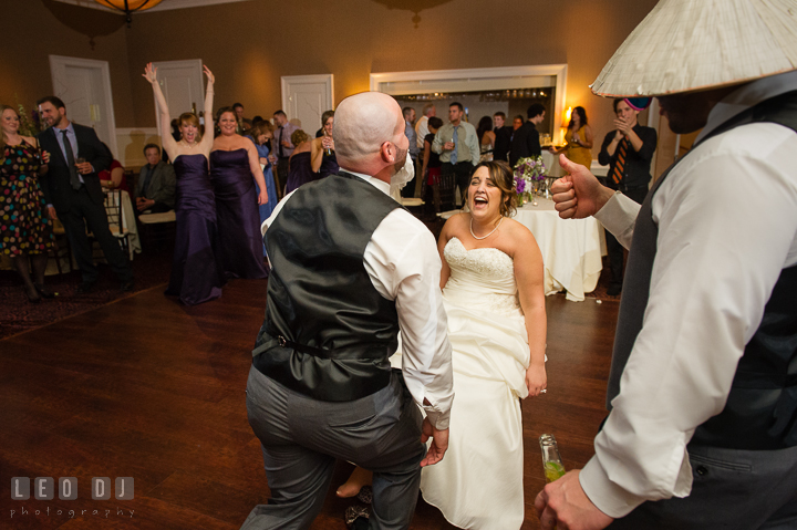 Bride laughing hard looking at Groom biting the garter. The Tidewater Inn Wedding, Easton Maryland, reception photo coverage by wedding photographers of Leo Dj Photography. http://leodjphoto.com