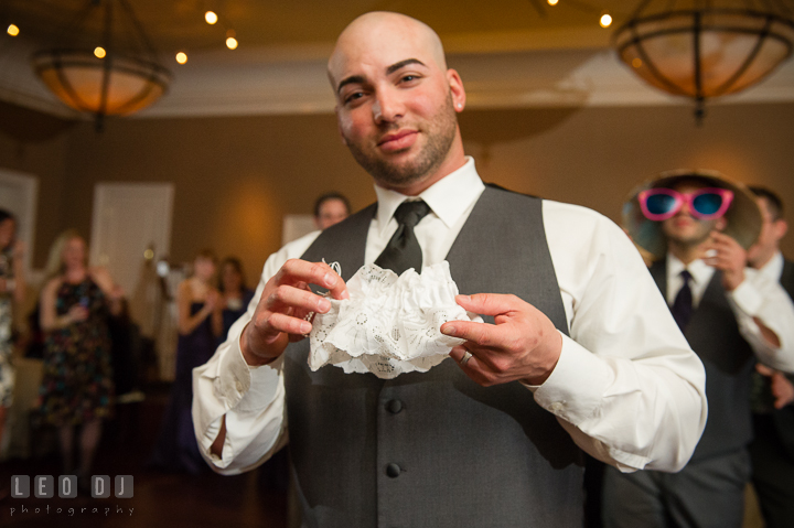 Groom holding the garter in his hands. The Tidewater Inn Wedding, Easton Maryland, reception photo coverage by wedding photographers of Leo Dj Photography. http://leodjphoto.com