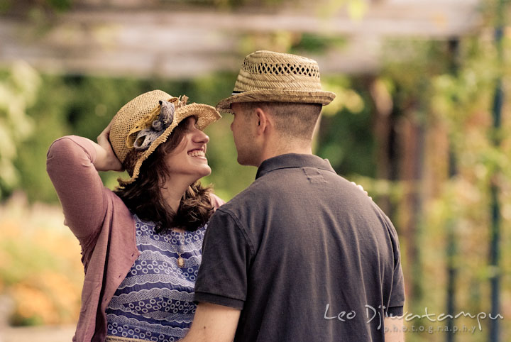Engaged girl wearing hat and smiling big to her fiancé. Pre-wedding engagement photo session at Brookside Gardens, Wheaton, Silver Spring, Maryland, by wedding photographer Leo Dj Photography.
