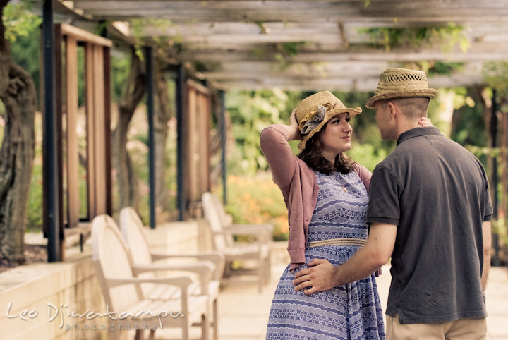 Engaged couple wearing hats smiling at each other. Pre-wedding engagement photo session at Brookside Gardens, Wheaton, Silver Spring, Maryland, by wedding photographer Leo Dj Photography.