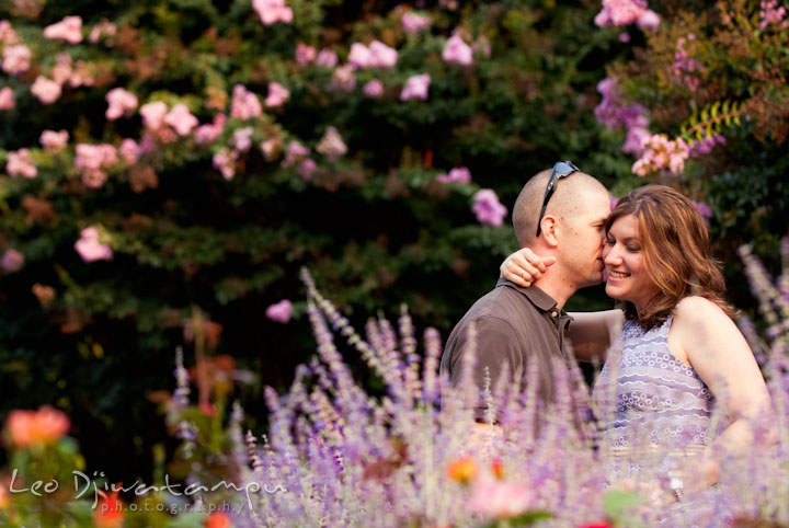Engaged guy whispers in his fiancée's ear amidst the flower garden. Pre-wedding engagement photo session at Brookside Gardens, Wheaton, Silver Spring, Maryland, by wedding photographer Leo Dj Photography.