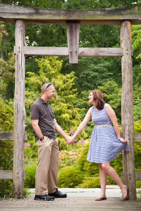 Engaged guy holding his fiancée under a Japanese gazebo arch. Pre-wedding engagement photo session at Brookside Gardens, Wheaton, Silver Spring, Maryland, by wedding photographer Leo Dj Photography.