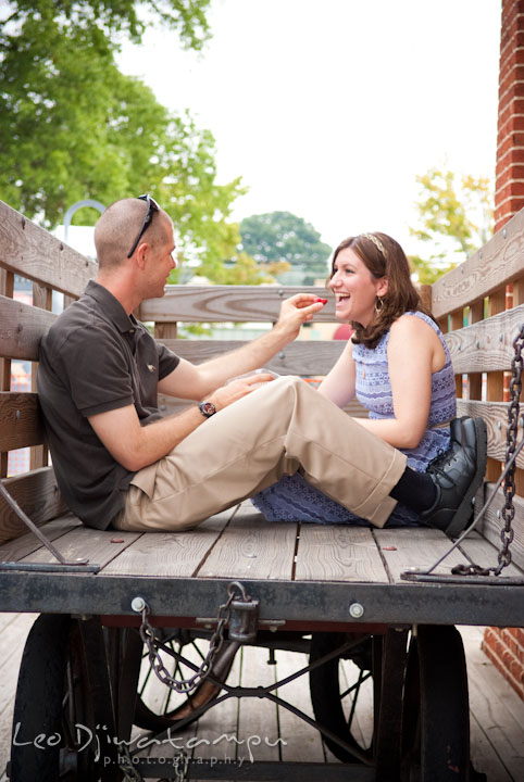 Engaged guy feeding his fiancée. Pre-wedding engagement photo session at Old Town Gaithersburg, Maryland, by wedding photographer Leo Dj Photography.