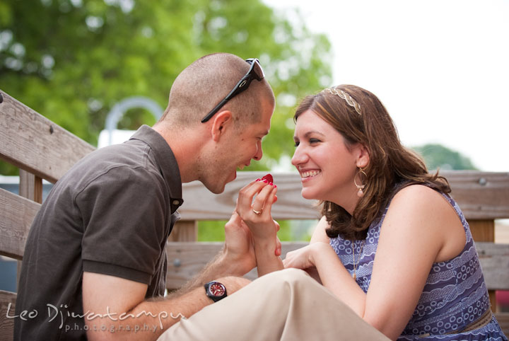 Engaged girl feeding her fiancé. Pre-wedding engagement photo session at Old Town Gaithersburg, Maryland, by wedding photographer Leo Dj Photography.