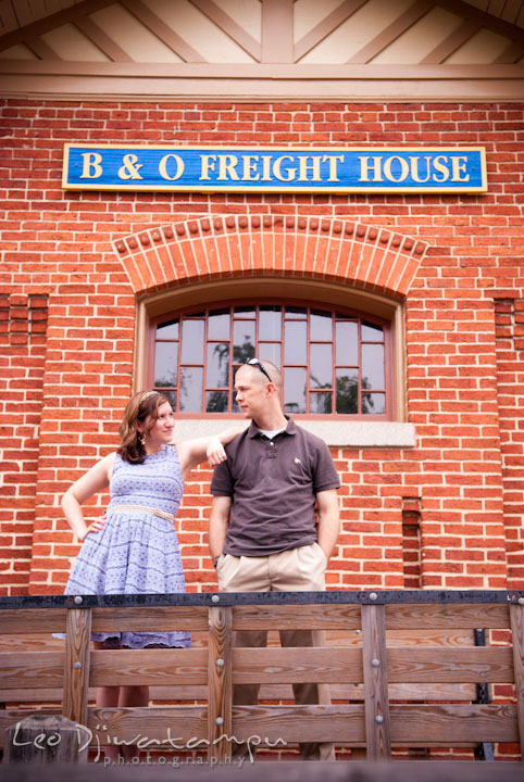 Engaged couple posing by an old B&O Train Freight House. Pre-wedding engagement photo session at Old Town Gaithersburg, Maryland, by wedding photographer Leo Dj Photography.