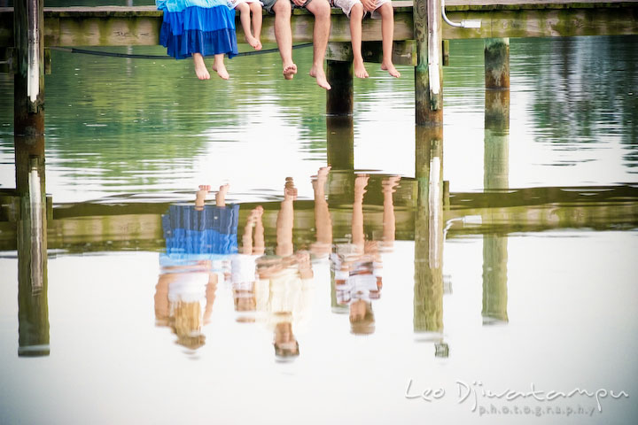 Feet and legs hanging from pier, with the family's shadow on the water. Kent Island and Annapolis, Eastern Shore, Maryland Candid Family Maternity Session Photographer
