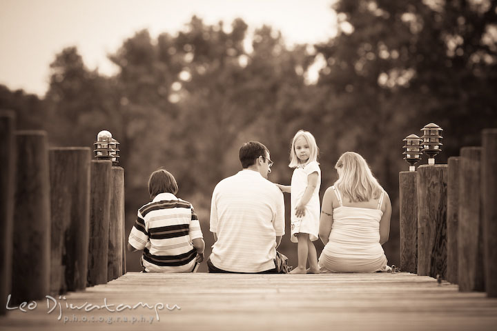 Family sitting on pier, little girl looking at camera. Kent Island and Annapolis, Eastern Shore, Maryland Candid Family Maternity Session Photographer
