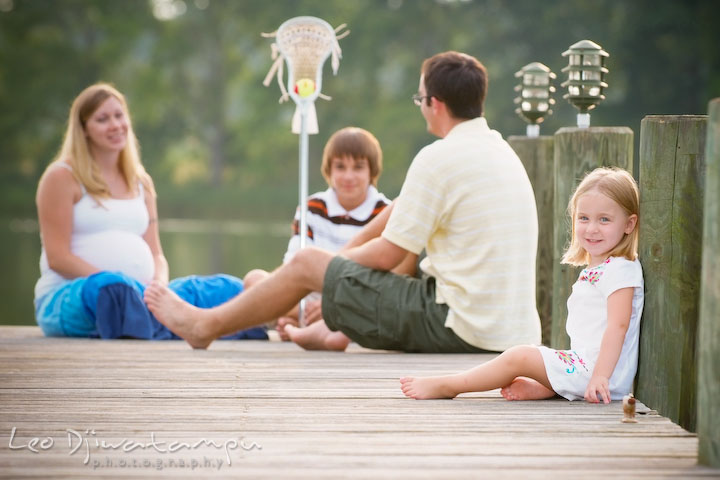 Little girl, daughter, posing on pier, family in the back. Kent Island and Annapolis, Eastern Shore, Maryland Candid Family Maternity Session Photographer