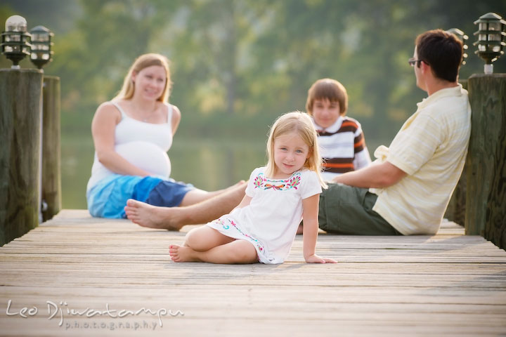 Little sister posing on the pier, family in the background, talking. Kent Island and Annapolis, Eastern Shore, Maryland Candid Family Maternity Session Photographer