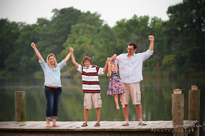 Family (mother, son, daughter, and father) standing on pier raising hands up in the air. Kent Island and Annapolis, Eastern Shore, Maryland Candid Family Maternity Session Photographer