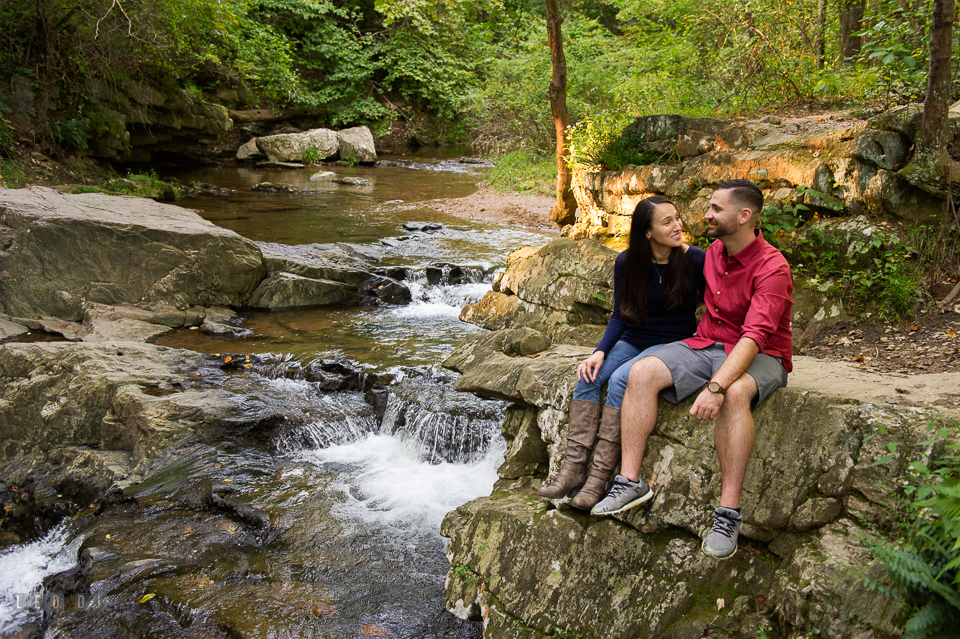 Rocks State Park Bel Air Maryland engaged couple sitting on rocks by a waterfall photo by Leo Dj Photography.