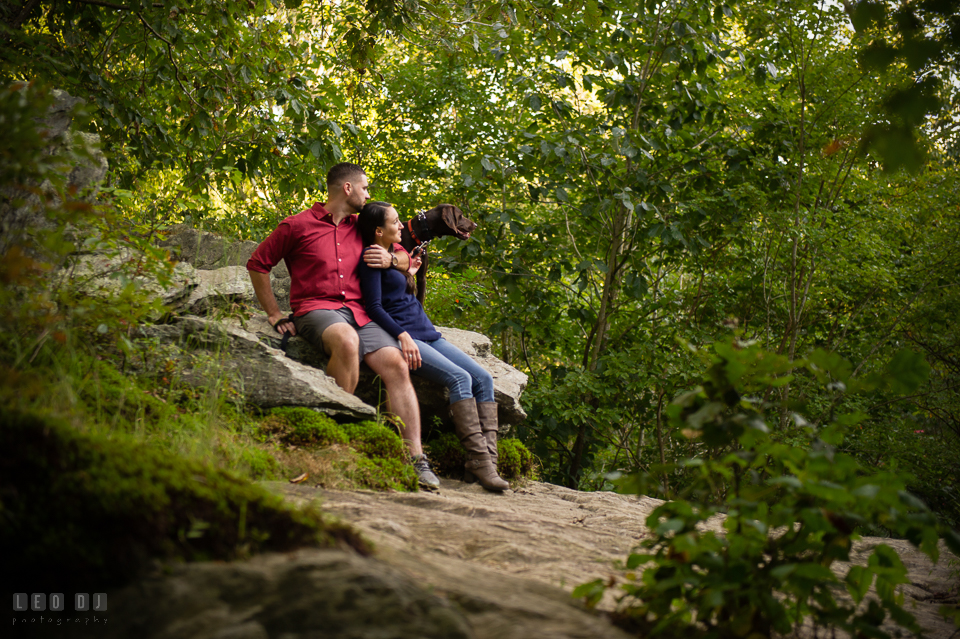 Rocks State Park Bel Air Maryland engaged couple cuddling accompanied with dog photo by Leo Dj Photography.