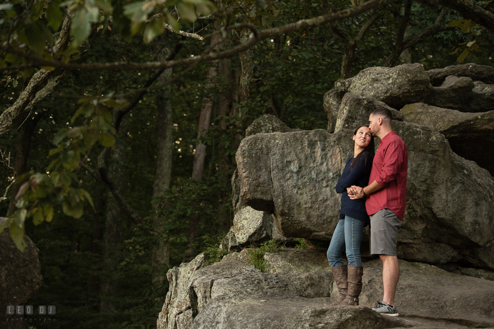 Rocks State Park Bel Air Maryland engaged man hugging and kissing fiancée photo by Leo Dj Photography.