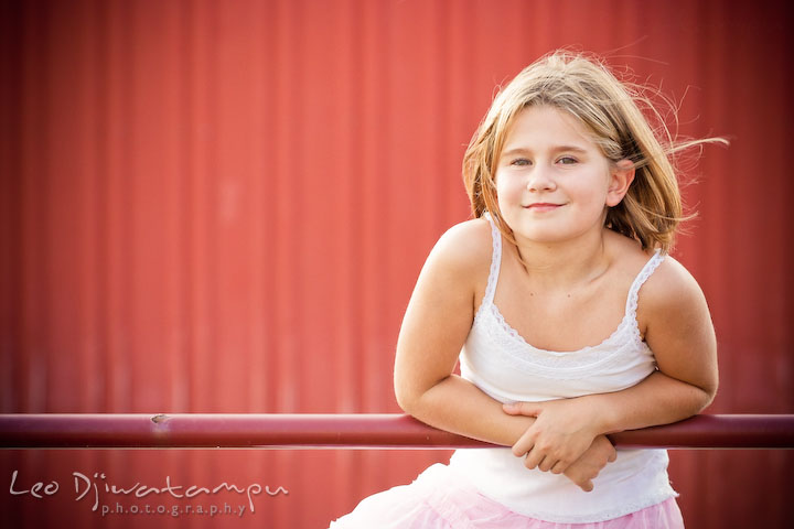 Girl posing on red fence gate with red background. Kent Island, Annapolis Maryland candid children lifestyle portrait photo at beach and farm