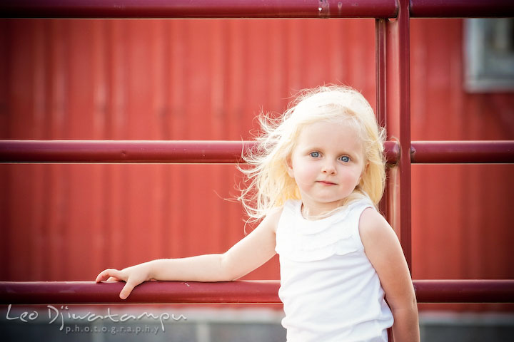Little toddler girl with blond hair posing by a red fence. Kent Island, Annapolis Maryland candid children lifestyle portrait photo at beach and farm