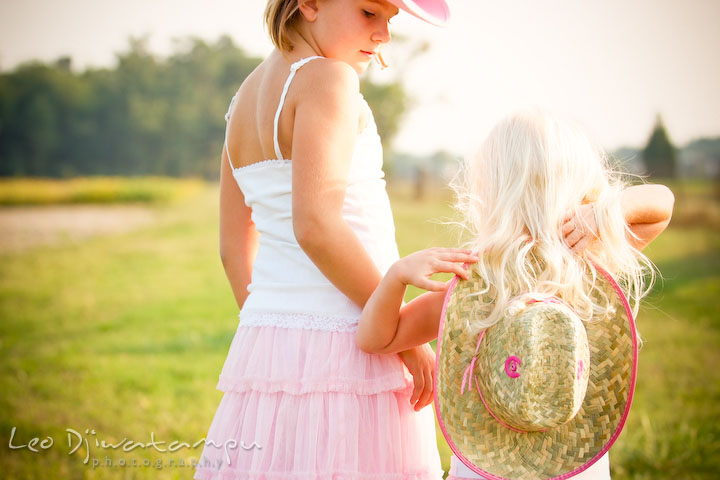 Sisters with cowboy hat in the meadow. Kent Island, Annapolis Maryland candid children lifestyle portrait photo at beach and farm