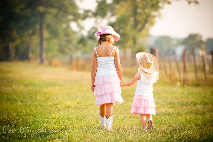Two girls walking together in a meadow holding hands. Kent Island, Annapolis Maryland candid children lifestyle portrait photo at beach and farm