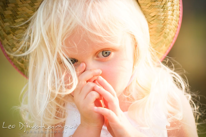 Blond girl with straw hat and blue eyes sucking thumb. Kent Island, Annapolis Maryland candid children lifestyle portrait photo at beach and farm